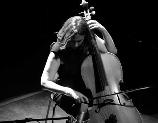 Long haired musician playing a cello on stage. Photo is black and white.
